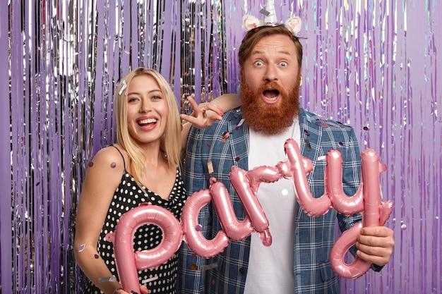 Concepto de personas y vacaciones. feliz pareja sorprendida mantenga globos de aire en forma de letras