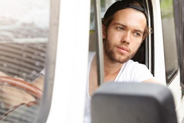 Concepto de personas, vacaciones y viajes. apuesto joven barbudo sentado dentro de su vehículo suv blanco y mirando por la ventana abierta con expresión alegre