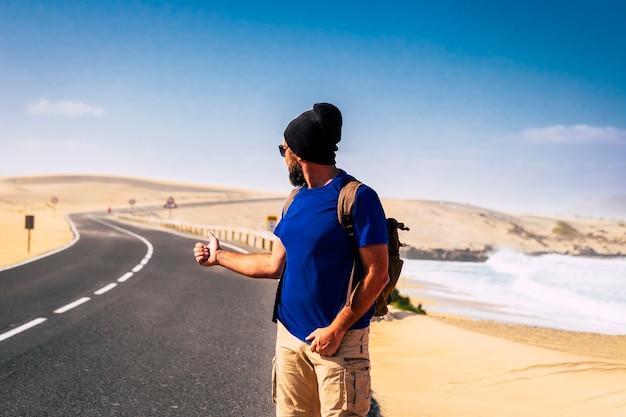Concepto de personas de viaje alternativo de hitcher con un hombre con una mochila esperando un coche para compartir el viaje viajeros solitarios con un largo camino y una aventura salvaje de vacaciones en el desierto y la playa de arena