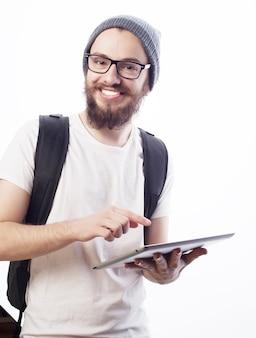 Concepto de personas, viajes, turismo y tecnología - feliz joven barbudo en anteojos con mochila y tableta sobre fondo blanco. estilo hipster. emociones positivas.