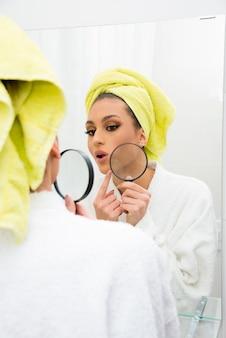 Concepto de piel seca y dañada o perfecta. mujer sosteniendo una lupa mirando su piel en el espejo vistiendo albornoz y toalla.