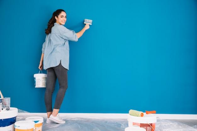 Concepto de pintura con mujer pintando pared azul