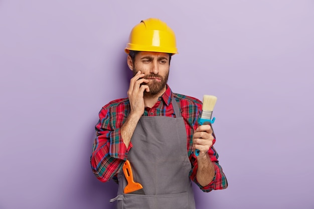 Concepto de pintura mural. el artesano serio y reflexivo mira un cepillo limpio, se muerde el labio inferior, piensa cómo comenzar la renovación de su apartamento, usa un casco amarillo y un delantal, aislado en una pared púrpura
