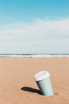 Concepto de playa con vaso de papel