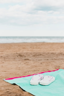 Concepto de playa con zapatillas en toalla