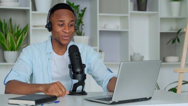 Concepto de podcast feliz joven blogger de audio negro en auriculares con computadora portátil y micrófono de radiodifusión en casa apagado