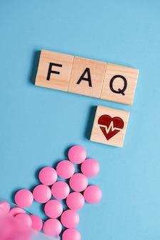 El concepto de preguntas básicas y generales sobre medicamentos, píldoras para el corazón. tabletas de color rosa junto al cuadrado de madera y letras - preguntas frecuentes.