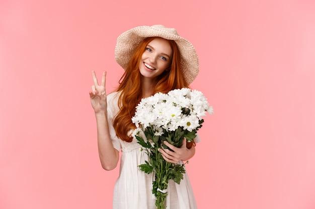 Concepto de primavera, celebración y emociones. alegre pelirroja encantadora mujer en lindo sombrero de paja