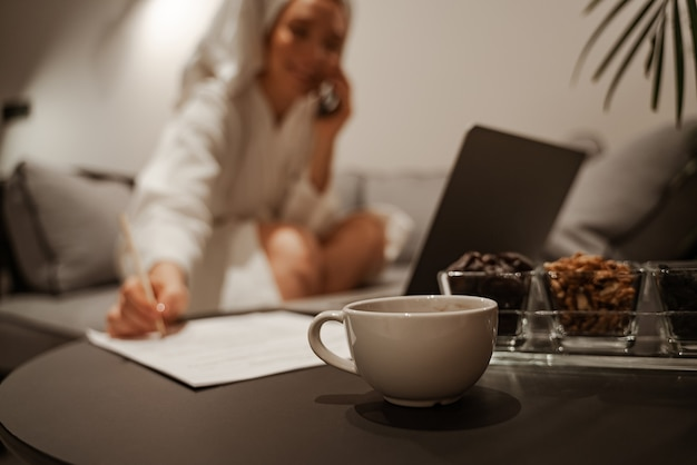 Concepto de primer plano. una mujer de negocios con una túnica blanca y una toalla usa una computadora portátil y bebe té o café. se sienta en el sofá y escribe documentos. relajación nocturna.