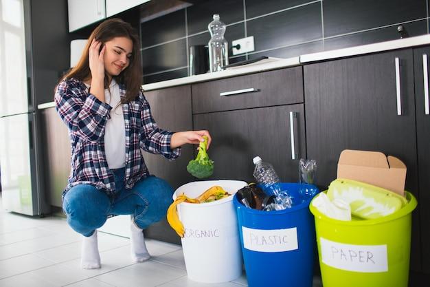 Concepto de primer plano. ordenar basura en casa. hay tres cubos para diferentes tipos de basura. mujer joven clasifica los desechos en la cocina
