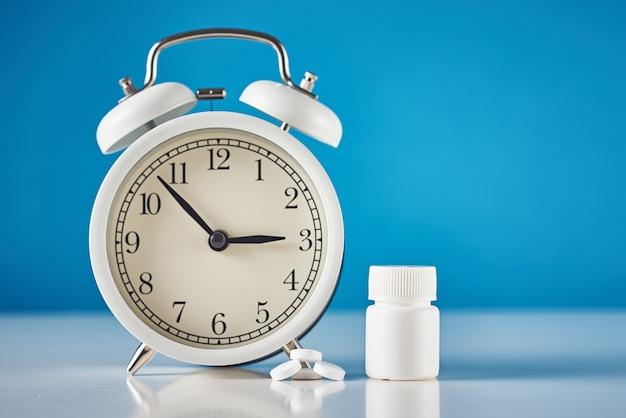 Concepto de problema de insomnio. despertador y pastillas sobre fondo azul.