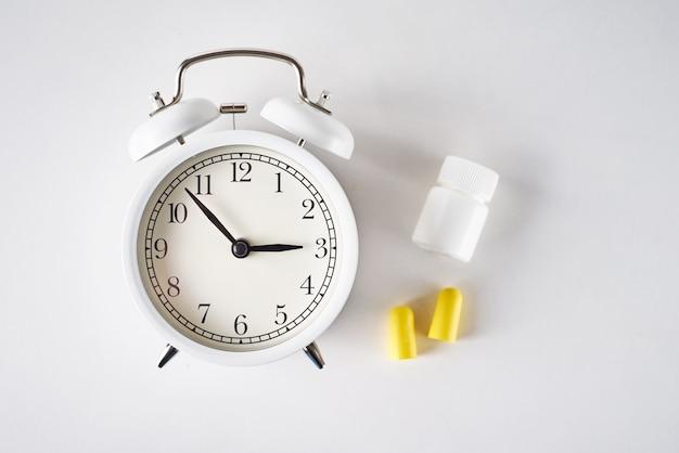 Concepto de problema de insomnio. despertador, tapones para los oídos y pastillas sobre fondo blanco.