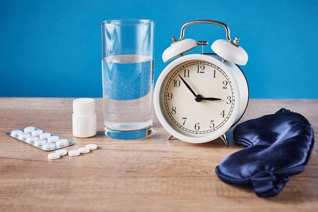 Concepto de problema de insomnio. despertador, vaso de agua y pastillas sobre fondo azul.
