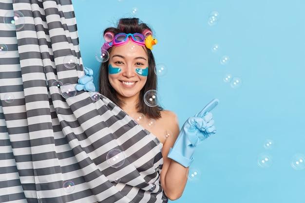 Concepto de procedimientos de belleza y cuidado corporal diario. sonriente niña morena alegre aplica rizadores de pelo y almohadillas de colágeno para el cuidado de la piel debajo de los ojos