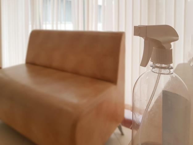 El concepto de procesamiento y desinfección de muebles en una oficina o en un apartamento residencial, una botella de spray con antiséptico en primer plano, un sofá de cuero en el fondo.