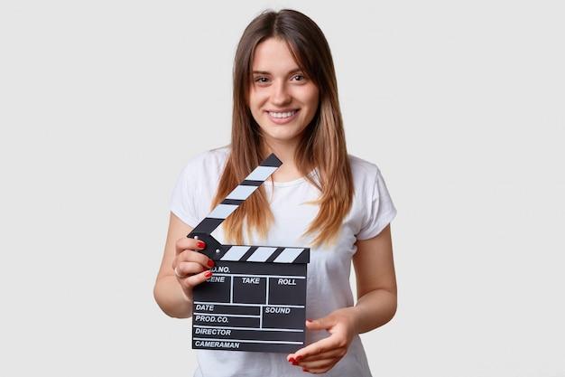 Concepto de productividad cinematográfica. hermosa mujer joven sonriente contenta tiene tablero de badajo en movimiento
