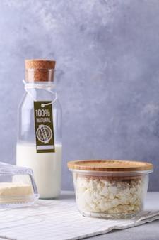 Concepto de productos lácteos en botella gris de leche con etiqueta de productos naturales requesón y mantequilla