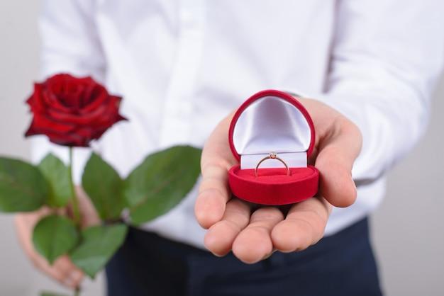 Concepto de propuesta de matrimonio. primer plano recortado de abierto con hermoso anillo dorado con pared gris aislada de piedra grande