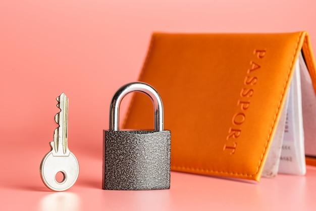 Concepto de protección de derechos de emigración, llave y candado con pasaporte.