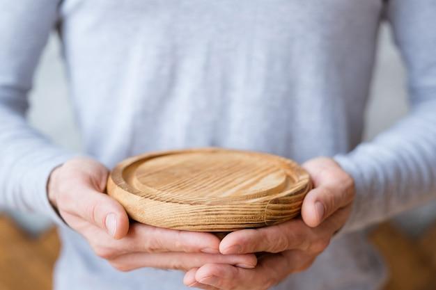 Concepto de protección de la naturaleza. bandeja de madera en manos del hombre.