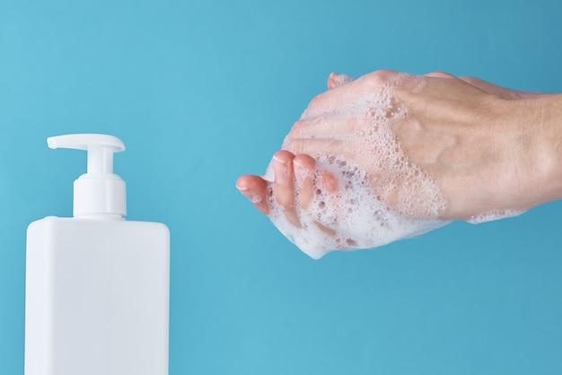 Concepto de protección de la salud del brote de covid-19 con antiséptico. mujer lavarse las manos con desinfectante o gel antiséptico como medida de prevención para el coronavirus sobre fondo azul.