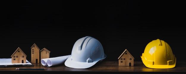 Concepto de proyecto inmobiliario, inmobiliario y de construcción, herramientas de ingeniero con pequeña casa de madera o casa sobre mesa en fondo oscuro