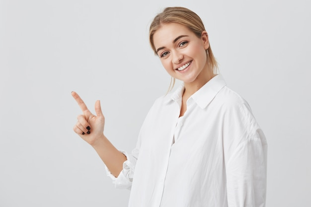 Concepto de publicidad. feliz mujer joven con cabello rubio con ropa casual, de pie con espacio de copia para su información o contenido promocional