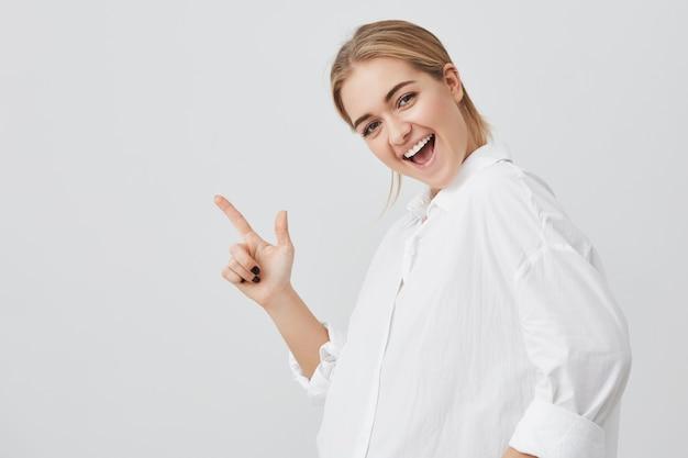Concepto de publicidad. mujer joven guapa con cabello rubio con ropa casual, sonriendo alegremente dientes, de pie con espacio de copia para contenido promocional