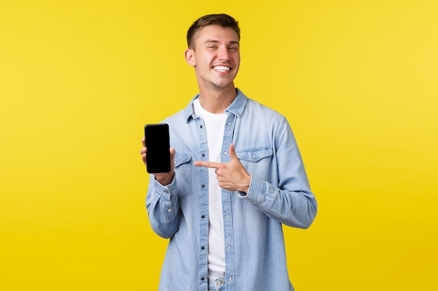 Concepto de publicidad de ocio, tecnología y aplicaciones. orgulloso feliz sonriente chico rubio recomendando la aplicación de teléfono inteligente, señalando con el dedo al teléfono móvil para presumir con sus imágenes, fondo amarillo.