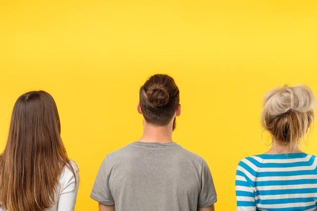 Concepto de publicidad. vista posterior de tres personas mirando un objeto imaginario. copie el espacio en la pared amarilla.