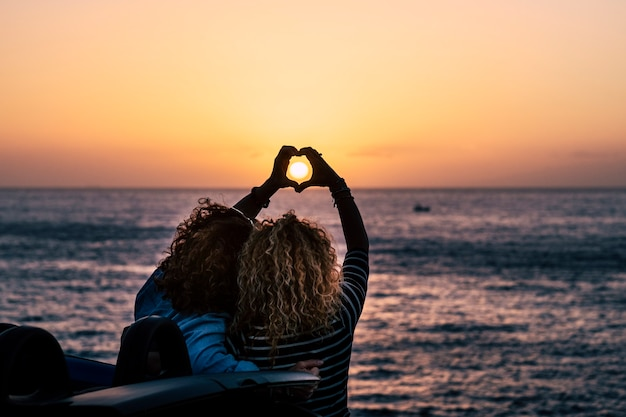 Concepto de pueblo de amistad romántica con dos dama rizada vista desde atrás haciendo signo de amor de hogar con las manos para celebrar el viaje de vacaciones de verano frente a la belleza del océano de la naturaleza