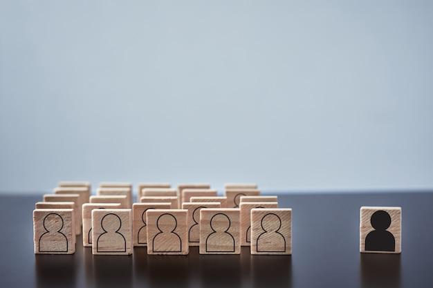 Concepto de racismo y malentendido entre personas, prejuicios y discriminación. bloque de madera con figuras de gente blanca y una con fondo de hombre negro