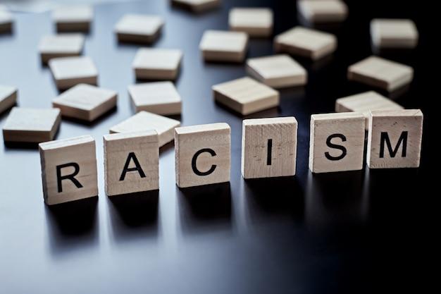 Concepto de racismo y malentendido entre personas, prejuicios y discriminación. bloque de madera con la palabra racismo en el fondo negro