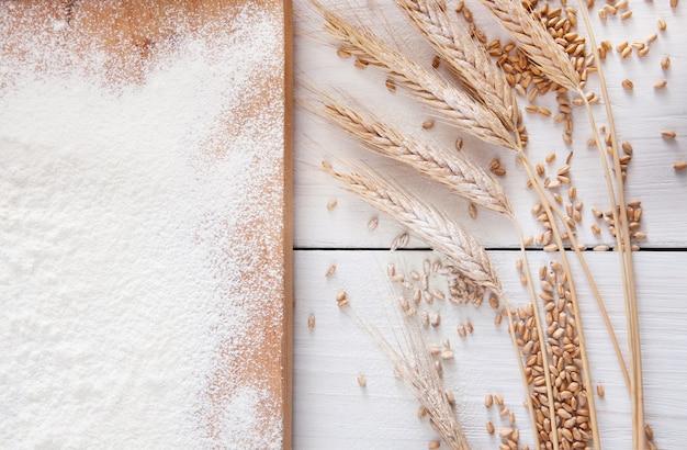 Concepto de receta o clase de cocción, espolvoreado con harina de trigo, granos y espigas. vista superior sobre tablero de madera en la mesa. cocinar masa o pastelería.