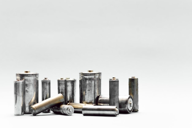 Concepto de reciclaje ecológico, energía de la naturaleza, muchos tipos diferentes, batería usada, acumulador recargable, baterías alcalinas sobre fondo blanco.