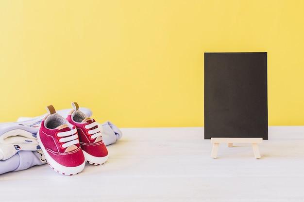 Concepto de recién nacido con tabla y zapatos