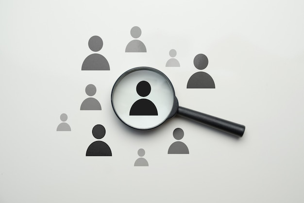Concepto de recursos humanos de búsqueda de empleados - lupa con empleado abstracto en un espacio en blanco.