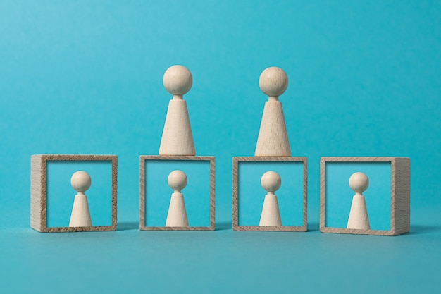 Concepto de red social y comunicación a través de una pantalla figuras de madera sobre fondo azul.