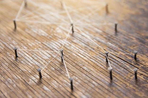 Concepto de redes conectadas - red conectada con hilo blanco en madera de tablones con copia espacio.