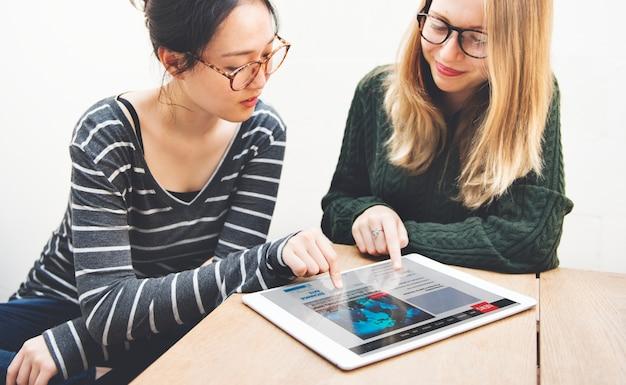Concepto de redes de noticias de la tableta digital de la amistad de las mujeres