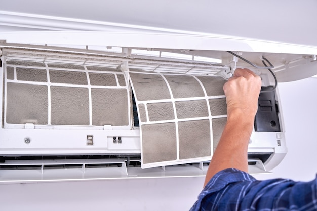 El concepto de reemplazar y limpiar filtros sucios para un acondicionador de aire doméstico