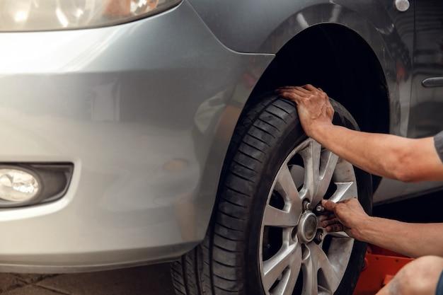 Concepto de reemplazo de neumáticos. mecánico trabajando su trabajo con la rueda en el garaje. mantenimiento de automóviles y servicios