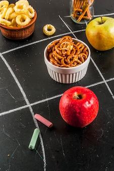 Concepto de refrigerio saludable y poco saludable de tres en raya con galletas, papas fritas y manzanas
