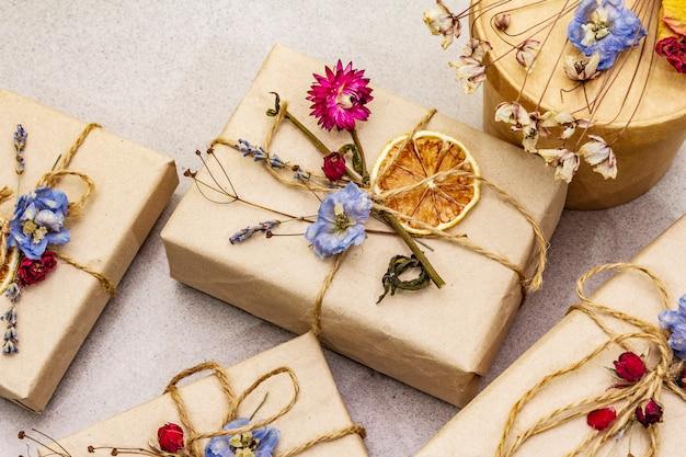 Concepto de regalo cero desperdicio. embalaje ecológico de cumpleaños. cajas festivas en papel artesanal con diferentes decoraciones orgánicas.