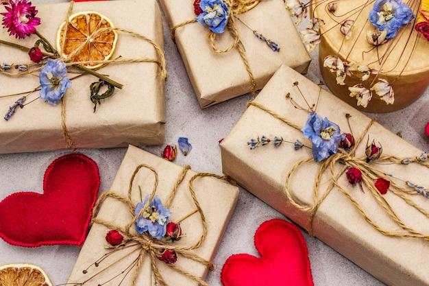 Concepto de regalo cero desperdicio. embalaje ecológico de san valentín o cumpleaños. cajas festivas en papel artesanal con diferentes decoraciones orgánicas.