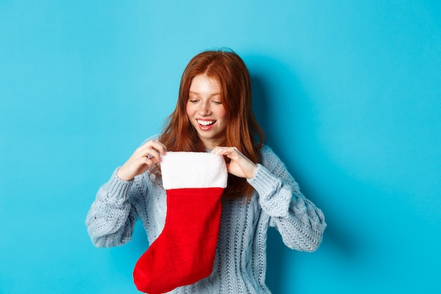 Concepto de regalos y vacaciones de invierno. chica pelirroja divertida mirando dentro de la media de navidad y sonriendo feliz, recibiendo regalo de navidad, de pie contra el fondo azul.