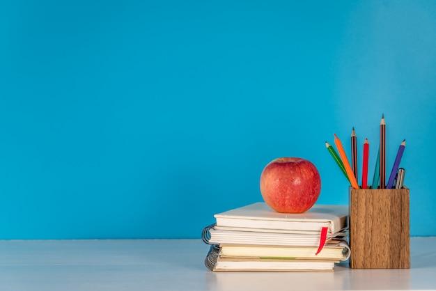 Concepto de regreso a la escuela apple y útiles escolares en mesa blanca