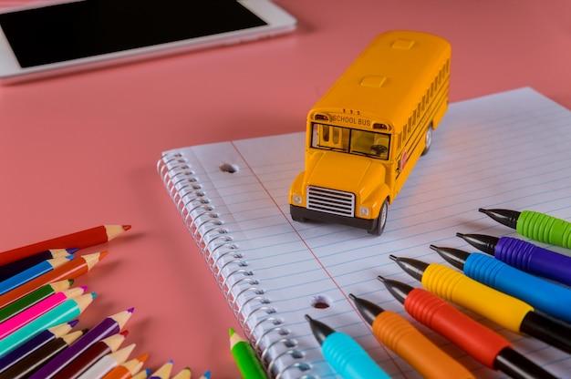 Concepto de regreso a la escuela, autobús escolar en cuaderno y lápices