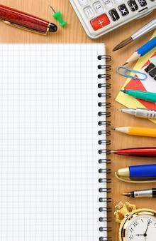 Concepto de regreso a la escuela y cuaderno comprobado sobre fondo de madera