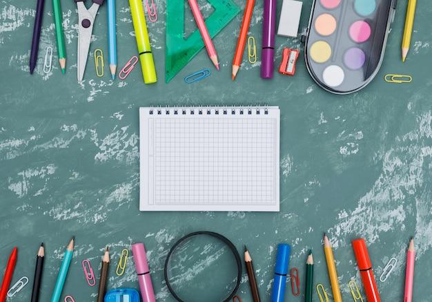 Concepto de regreso a la escuela con cuaderno, lupa, útiles escolares en fondo plano de yeso.